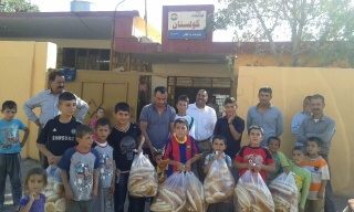 Yezedi Refugee Families sheltering in school building receive fresh bread.